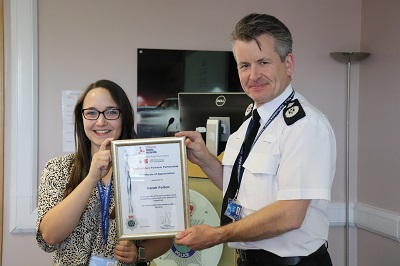 Sarah Felton receiving a certificate from Deputy Chief Constable Nick Baker.