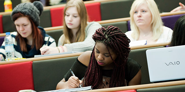 student taking notes in a lecture theatre
